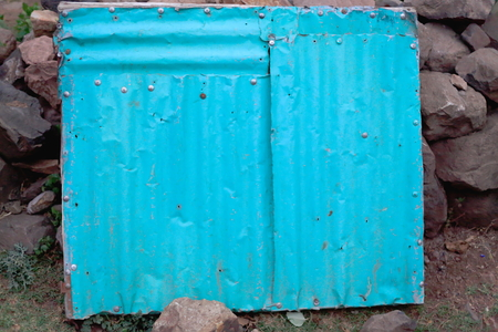 dry stone: Tin door painted blue on the dry stone wall of a house in the area surrounding Gebriel Bete-Saint Gabriel orthodox christian church. Kombolcha town at 1842 ms.-Debub Wollo zone-Amhara region-Ethiopia.