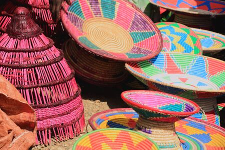 sunday market: Traditional colorist basketry -plates-containers-receptacles- for sale on a stall in the sunday market where the Oromo-Amhara-Afar peoples meet . Senbete-Oromia zone-Amhara region-Ethiopia. Stock Photo