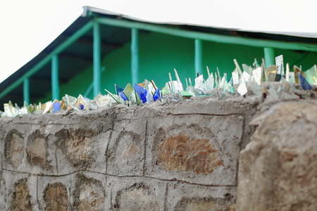 glass topped: Stone and concrete wall topped with broken glasses for security of a local house. Kombolcha town at 1842 ms.-Debub Wollo zone-Amhara region-Ethiopia.
