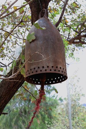 religious service: Rusty old iron bell hanging from a tree inside the compound of the Gebriel Bete-Saint Gabriel orthodox christian church. Kombolcha town at 1842 ms.-Debub Wollo zone-Amhara region-Ethiopia.