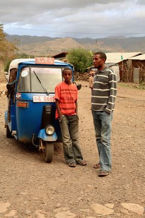 three wheeler: KOMBOLCHA, ETHIOPIA-MARCH 24: Man and boy wait beside an autorick outside Bete Gebriel-St.Gabriel church compound for the religious service to begin on March 24, 2013. Debub Wollo zone-Amhara region.