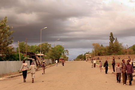 attended: KOMBOLCHA, ETHIOPIA-MARCH 24: Local people stroll under stormy skies on Sunday evening after having attended church on March 24, 2013. Debub Wollo zone-Amhara region.