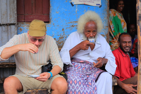 amharic: DEGAN, ETHIOPIA-MARCH 25: Local VIP shares a cup of coffee with a tourist visiting the khat market being held in the town on March 25, 2013. Debub Wollo zone-Amhara region. Editorial