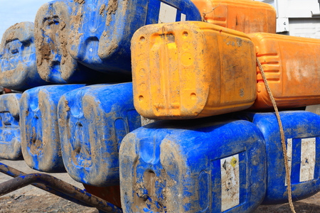 salt marsh: Big blue-yellow plastic jerrycans-empty and piled on an iron wheelbarrow placed on the main-unique street of Afrera town beside the Lake Afrera Saltworks. Administrative zone 2-Afar region-Ethiopia. Stock Photo