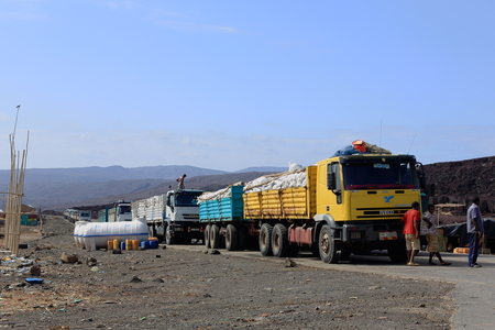workingman: AFRERA, ETHIOPIA-MARCH 26: Workers load a row of yellow-blue-white trucks with salt sacks from the nearby Afrera Lake Saltworks ready for transport on March 26, 2013. Admin.zone 2-Afar region-Ethiopia