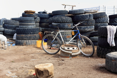 leaning on the truck: White and blue iron mountain bike leaning on a truck rim placed among old truck tires on the main street of Afrera town-born for the Afrera lake saltworks exploitation. Adm.zone 2-Afar region-Ethiopia Stock Photo