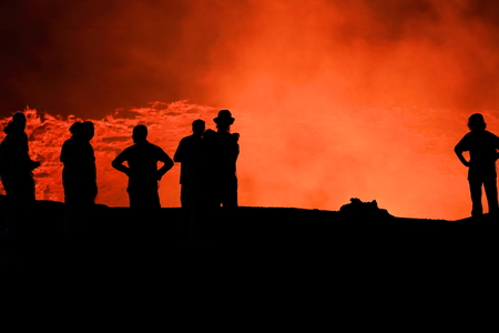 Tourists watching the world longest existing burning lava lake dating from 1906. Erta Ale basaltic shield volcano at 613 ms.high-eliptic crater of 0.7 x 1.6 km. Danakil desert-Afar region-Ethiopia. Foto de archivo