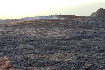 badland: Solid lava field-caldera of world longest existing burning lava lake dating from 1906-Erta Ale basaltic shield volcano at 613 ms.high-0.7 x 1.6 km.elliptic crater. Danakil desert-Afar region-Ethiopia. Stock Photo