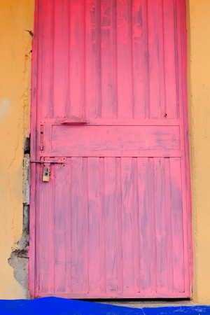 pedagogical: Pink painted-padlock closed metallic door on the mustard colored walls of the local school at Berahile town on the limits of the Danakil desert. Administrative zone 2-Afar region-Ethiopia.