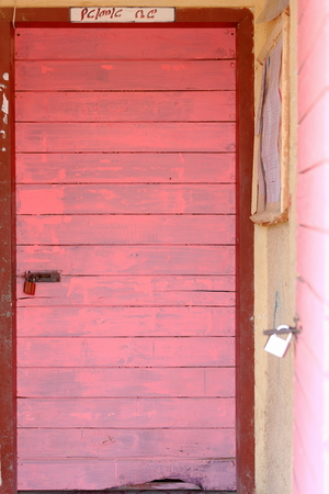 pedagogy: Pink painted-padlock closed wooden doors on the mustard colored walls of the local school at Berahile town on the limits of the Danakil desert. Administrative zone 2-Afar region-Ethiopia.