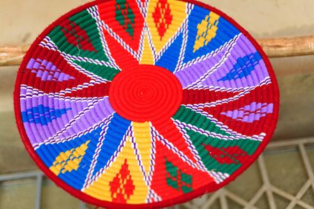 many colored: Hand made many colored basketry underplate for injera food with ethiopian decorative patterns. Handicraft shop in Mekele-Mekelle town at 2084 ms.high in Debubawi-Southern zone. Tigray region-Ethiopia Stock Photo