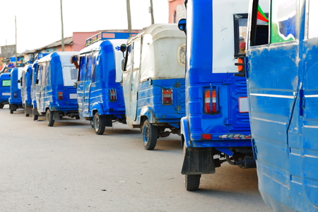 bajaj: Row of white and blue painted local auto rickshaw-tuk tuk-baby taxi-mototaxis stationed on a street of central Mekele-Mekelle town at 2084 ms.high in Debubawi-Southern zone. Tigray region-Ethiopia.