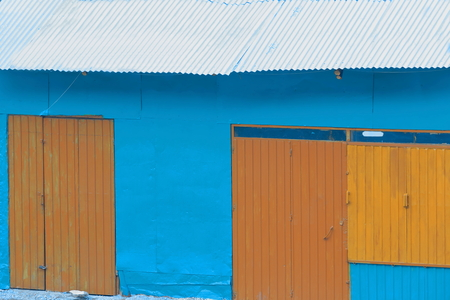 brownish: Blue painted wall-closed brownish metal doors-blue tin roof of building-warehouse facing the terrace of the Hikma Pension-Hotel. Kombolcha town at 1842 ms.high-Debub Wollo zone-Amhara region-Ethiopia.