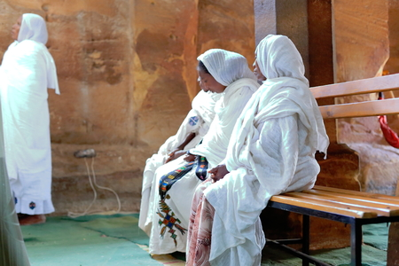 religious service: WUKRO, ETHIOPIA-MARCH 29: Orthodox christian devotees attend religious services dressed in habesha kemis and netela white clothes on March 29, 2013 in Wukro Chirkos rock-hewn church. Tigray region.