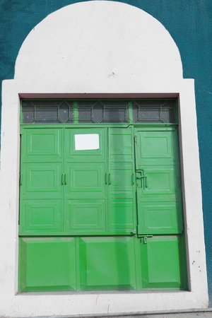 glass topped: Green painted metal-windowglass topped closed door of store on white and blue painted wall-commercial building in Mekele-Mekelle town and special zone. Debubawi-Southern zone. Tigray region-Ethiopia.