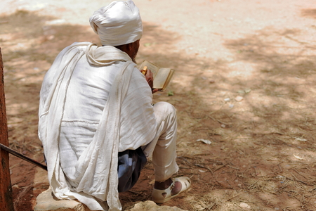 devotee: WUKRO, ETHIOPIA-MARCH 29: Ethiopian orthodox christian devotee man with white gabi dress reads a sacred book while seated on a stone on March 29, 2013. Outside Wukro Chirkos rock-hewn church in Wukro town-Misraqawi zone-Tigray region.