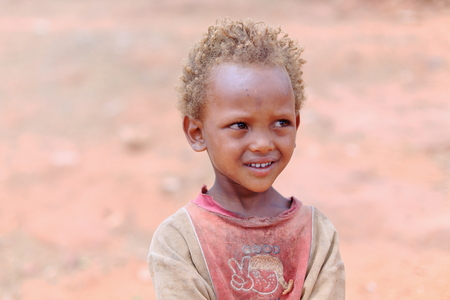 religious service: WUKRO, ETHIOPIA-MARCH 29: Fair-haired boy waits for his father to exit the Wukro-Chirkos rock-hewn church after the religious service on March 29, 2013. Wukro-Tigray region-Ethiopia. Editorial