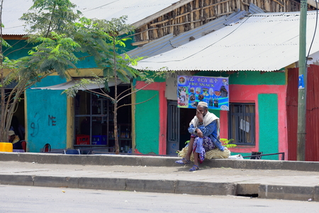 mates: MAYCHEW, ETHIOPIA-MARCH 30: Tigrayan man seats over a rope bundle on the sidewalk at the entry to a snack-bar and waits for mates to have coffee on March 30, 2013. Mekele-Mekelle town-Tigray region.