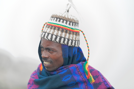 offish: DEBRE BIRHAN, ETHIOPIA-MARCH 30: Amharic man wears horse hair hat as example of the local use for headdresses on March 30, 2013 in Meneliks Window mountain gorge near Debre Sina-Amhara region Editorial