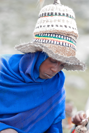 offish: DEBRE BIRHAN, ETHIOPIA-MARCH 30: Amharic man wears several horse hair hats as example of the local use for headdresses on March 30, 2013. Meneliks Window mountain gorge near Debre Sina-Amhara region