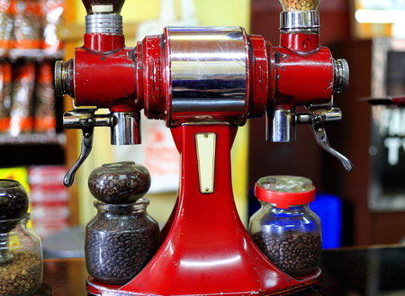 Red painted old italian style vintage coffee grinder along with glass jars containing roasted coffee beans ready to be ground in the Tomoca Coffee Shop of Piazza-downtown area. Addis Ababa-Ethiopia.
