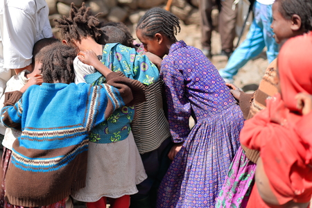 kinky: OROMIA, ETHIOPIA-MARCH 31: Local girls and boys swirl around a tourist visiting their hamlet and offering some candies to them on March 31, 2013. Village alongside the Debre Sina-Addis Ababa route.