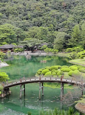 gosanke: TAKAMATSU, JAPAN-OCTOBER 19: Ritsurin Koen-Chestnut Grove Garden offers boat trips to the visitors on the Nanko-S.Pond and under Engetsu Kyo-Crescent Moon bridge on October 19, 2013. Takamatsu-Japan.