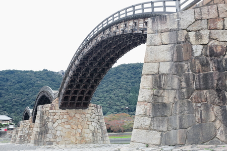 The AD.1673 built Kintai Kyo-bridge spans Nishiki river-foot of Mt.Shiroyama and Iwakuni castle-series of 5 wooden arches over 4 stone central+2 wooden final piers. Iwakuni-Yamaguchi pref.-Honshu-Japan Editorial