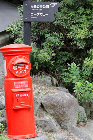 Signpost marking two tourist attractions in Itsukushima island-popularly Miyajima or Shrine island and red mailbox of Japan Post-inland side of the village around the shrine. Hatsukaichi city-Japan. Editorial