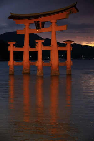 lacquerware: The c.500-600 years old-camphor tree-rotting resistant-vermilion lacquered main pillars+cedar tree sleeve pillars Itsukushima shrine Great Torii-gate at dusk-half tide. Miyajima-Hatsukaichi city-Japan