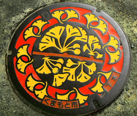 Round iron culvert lid decorated with red-yellow floral motifs on black background on the floor of a street of downtown Kumamoto city. Kumamoto prefecture-Kyushu island-Japan. Editorial
