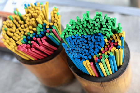 Multi-colored incense sticks placed in wooden cylindrical pannikins for sale to the devotees visiting the Hase-dera or Hasse-Kannon buddhist temple in Kamakura-Kanagawa prefecture-Japan.