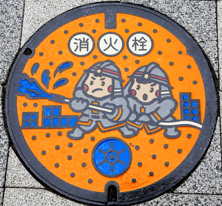 Round iron culvert lid for the firemen.s use decorated with a drawing of firemen fighting against fire on the floor of a street of downtown. Roppongi district-Minato wad-Tokyo-Honshu island-Japan.