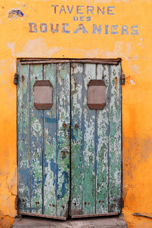 Peeling paint of old green door on yellow wall-tavern closed and out of operation facing the beach at the W.side of the harbor of the 198.2 hectare Goree island district of the city of Dakar-Senegal.