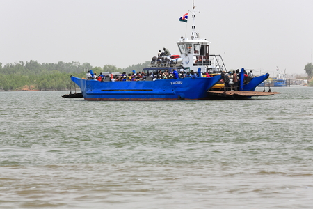 Yelitenda, The Gambia-April 14, 2014: Badibu named vehicle ferry crosses the Gambia river from Bambatenda-N.bank to Yelitenda-S.bank as part of the Trans-Gambia Highway on a c.10 minute-800 ms.trip.