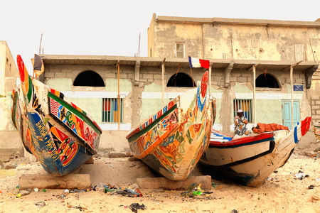 tinkered: Guet Ndar, St.Louis, Senegal-April 19, 2014: Two wolof men take a rest at their home.s door on the beach-port of Guet Ndar while waiting for their fishing piroque to come back with the day.s captures. Editorial