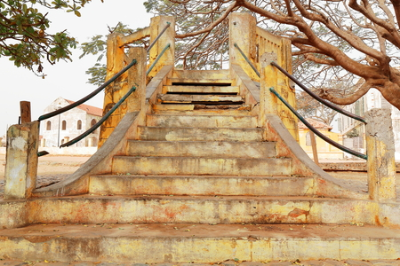goeree: Stairway leading to a ruined-concrete made-open air kiosk under a flamboyant tree beside the harbor and the beach in the middle of the central open space of Goree island district-Senegal.