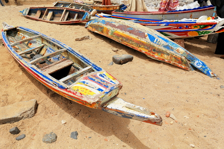 tinkered: Old wooden colorist fishing boats under the midday sun-seemingly out of order stranded on the sand of the beach inside the harbor of Goree island-district. Dakar-Senegal. Stock Photo