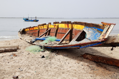 tinkered: Old wooden colorist fishing boat under the morning sun-ruined and out of order stranded on the sand of the beach facing the Casamance river mouth. Diogue island-Kafountine-Ziguinchor district-Senegal.