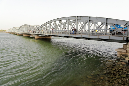 The July 14, 1897 opened Faidherbe metallic bridge spans the Senegal river linking the island-city of St.-Louis with the African mainland and has a 507.35 ms.total length-metal deck of riveted girders Foto de archivo