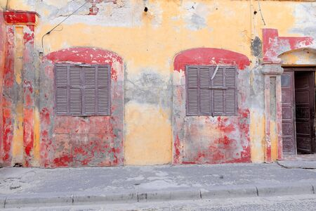 Yellow-ocher and vermilion facade of old French colonial house showing chipped areas along paint-faded zones and closed wooden shutters on windows. Historic town of Saint-Louis-du-Senegal city-island.