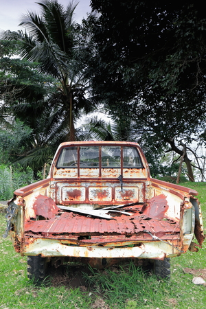 Rear view of the rusty-wormy-rotten remains of an old abandoned pickup truck in the grounds of the local school and church of Olal village at the N.tip of Ambrym island. Malampa province-Vanuatu. Foto de archivo