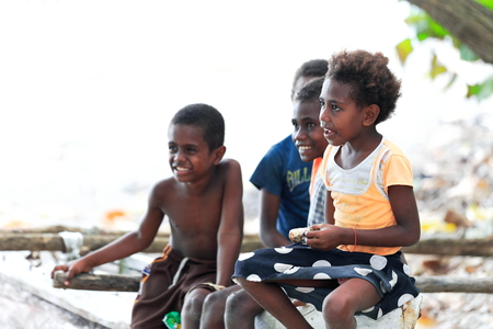 Lamen Bay, Epi island, Vanuatu-October 4, 2014: Four kids of the Ni-Vanuatu people take a rest to chat with the tourists after coming back from school while sitting on a fence waiting for lunch time. Editorial