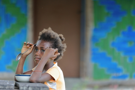 snotty: Lamen Bay, Epi island, Vanuatu-October 4, 2014: Young girl of the Ni-Vanuatu people unwillingly has lunch sitting at an outdoor table in front of her house after having arrived from school at midday.