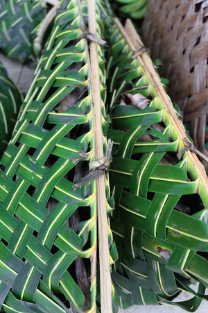 Traditional baskets made of braided coconut leaf for the transportation of vegetables and fruits on the concrete floor of the main market in Luganville-Espiritu Santo island-Sanma province-Vanuatu.