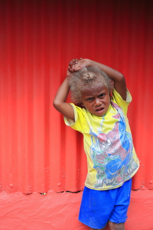 reluctant: Panngi, Pentecost island, Vanuatu-October 13, 2014: Young boy of the ni-Vanuatu people shows his curly blond hair as common genetic feature among them in spite of their black skin and racial traits.