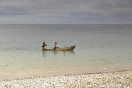 Panngi, Pentecost island, Vanuatu-October 14, 2014: Young boys of the ni-Vanuatu people cross the bay from South to North while paddling in their dugout canoe as the usual way of local transportation. Editorial