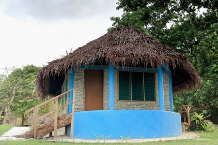 Blue painted thatched bungalow with veranda and masonry wall of coral stone among the tropical foliage of Lonnoc Beach. Hog Harbour village in the North East shore of Espiritu Santo island-Vanuatu. Foto de archivo