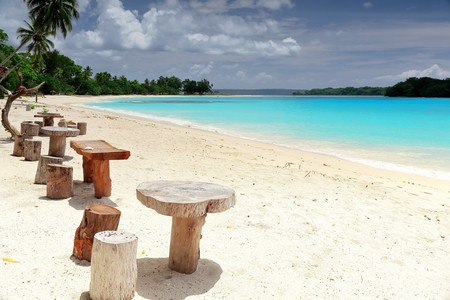 Set of wooden stools and tables for visitors placed under coconut palm trees on the white sands of the beach facing Malet island. Port Olry village in N.E.Espiritu Santo island-Sanma province-Vanuatu.