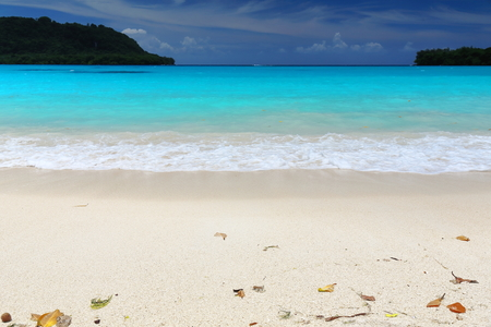 The coral white sands and quiet turquoise blue waters of the beach at Port Olry framed by Dolphin island to the North and Malmas island to the South. Espiritu Santo island-Sanma province-Vanuatu. Foto de archivo